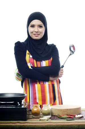 Beautiful muslim woman wearing scarf  smile to camera holding ladle isolated white background photo