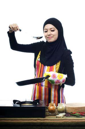 jasschort: Mooie moslim vrouw draagt sjaal smaak voedsel geïsoleerde witte achtergrond Stockfoto