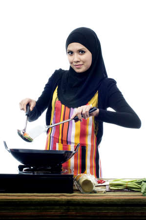 Beautiful muslim woman wearing scarf holding ladle busy cooking isolated white background