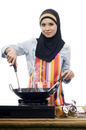 Beautiful muslim woman wearing scarf holding ladle in kitchen isolated white background