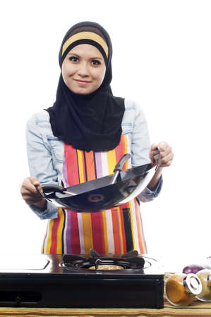 Beautiful muslim woman wearing scarf holding skillet looking to camera isolated white background