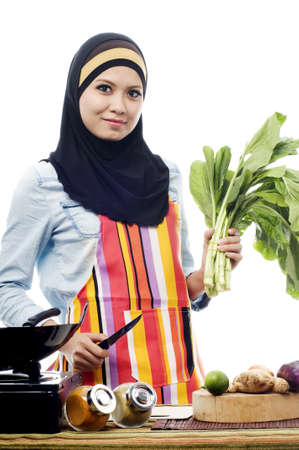 Beautiful muslim woman wearing scarf holding vegetables and knife isolated white background