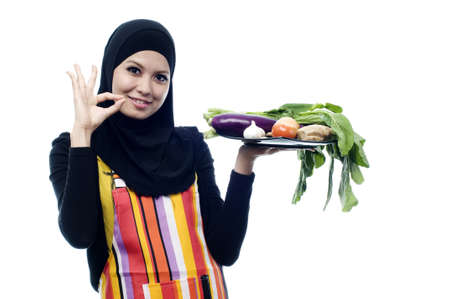 Beautiful muslim woman wearing scarf holding vegetables and show nice sign isolated white background Stockfoto