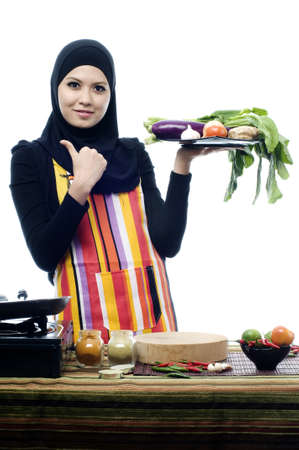 Beautiful muslim woman wearing scarf holding vegetables and show thumbs up isolated white background