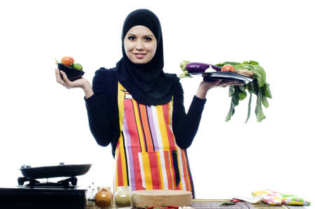 Beautiful muslim woman wearing scarf holding vegetables in left and right hands isolated white background