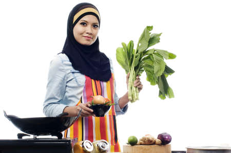 Beautiful muslim woman wearing scarf holding vegetables isolated white background