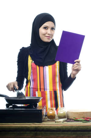 Beautiful muslim woman wearing scarf reading recepies while holding ladle isolated white background photo