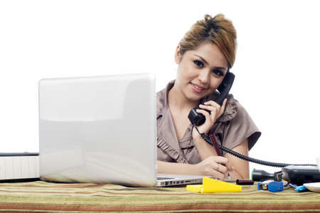 take a note: Beautiful young asian business woman answering phone call and take note isolated white background