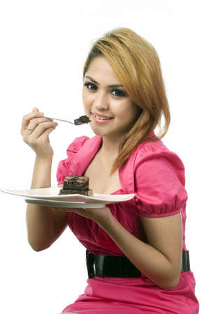 Beautiful young asian woman eating cake isolated white background photo