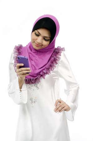 Mooie jonge moslim vrouw messaging op mobiele telefoon geà ¯ soleerd witte achtergrond Stockfoto