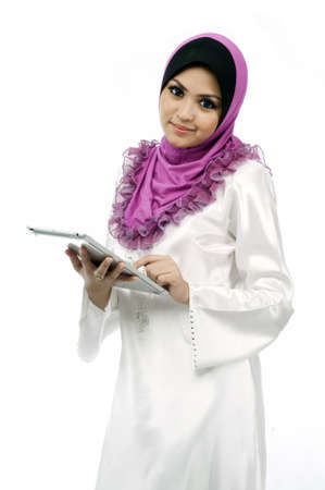 Beautiful young muslim woman messaging on mobile tab looking to front isolated white background