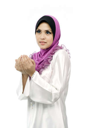Beautiful young muslim woman pray from side view isolated white background photo