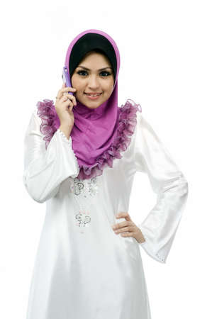 Beautiful young muslim woman talk on mobile phone isolated white background