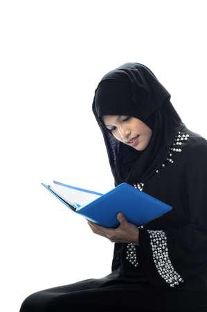 Mooie moslima's te bekijken haar laptop witte achtergrond