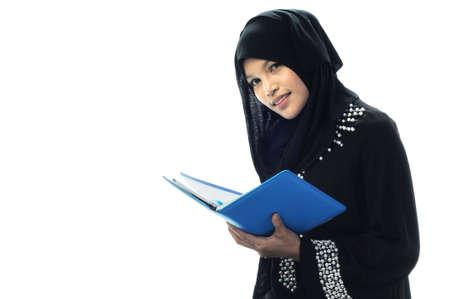 Mooie moslim womenhold haar laptop, terwijl glimlach witte achtergrond