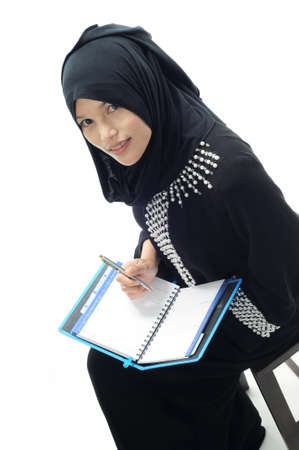 liberated: Muslim women look up while writing schedule isolated white background Stock Photo