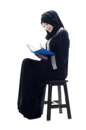 mujeres musulmanas: Hermosas mujeres musulmanas sentarse y leer un fondo blanco aislado
