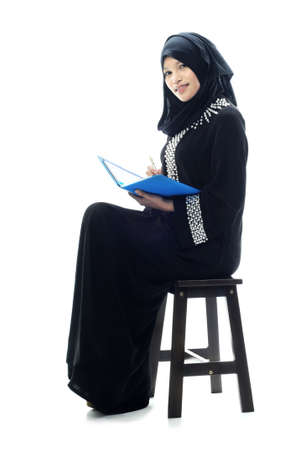 liberated: Beautiful muslim women smile while reading isolated white background