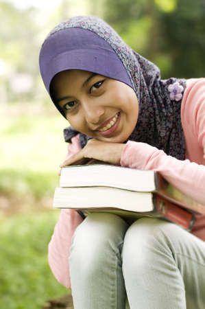 Beautiful young muslim lady holding book. She put her chin on her hand right on top of the book. Stock Photo