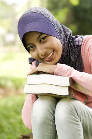 Mooie jonge moslim dame met boek. Ze legde haar kin op haar hand boven op het boek. Stockfoto