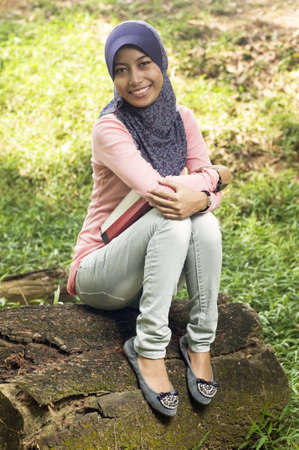 Beautiful young muslim lady hug book on the tree stump photo