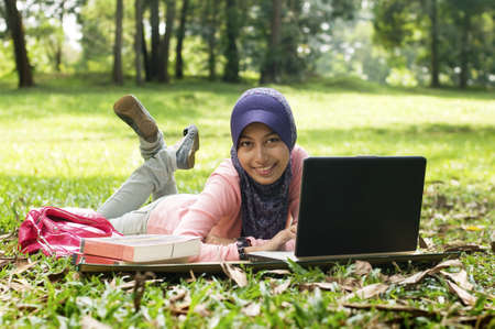 Beautiful young muslim lady lie down on the mat in front of notebook isolated green garden Stockfoto