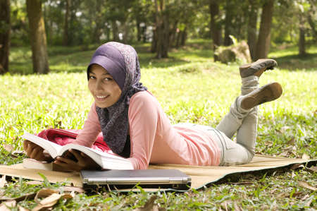 lie down: Beautiful young muslim lady lie down reading on the mat isolated green garden