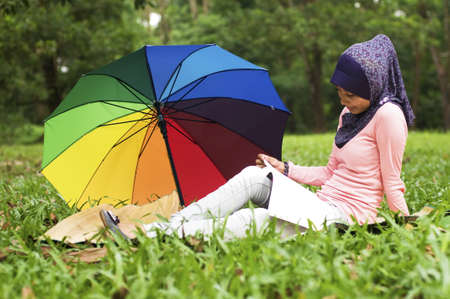 Beautiful young muslim lady read book isolated colorful umbrella and green forest photo