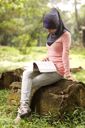 Beautiful young muslim lady sit on the stump reading isolated green park