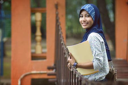 Mooie jonge moslim dame glimlach terwijl boeken op de brug in het park Stockfoto