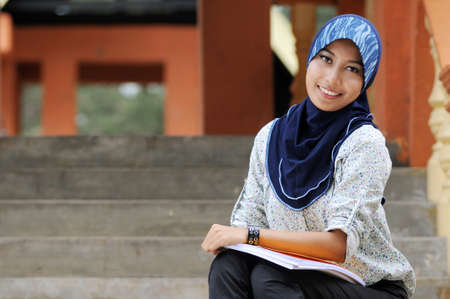 Beautiful young muslim lady smile while holding books at the park isolated stairs in blur Stockfoto