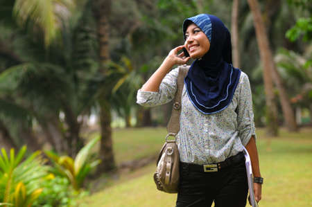Beautiful young muslim lady smile while talk to the phone isolated green park Stock Photo