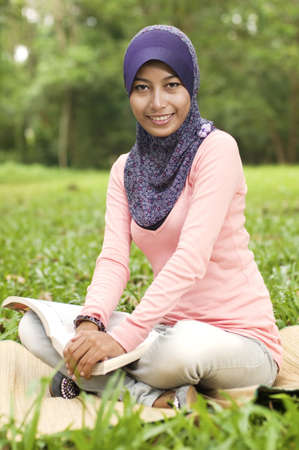 Beautiful young muslim lady smiling holding book isolated green field photo