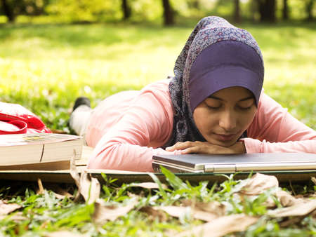 Beautiful young muslim lady take a nap isolated green garden photo
