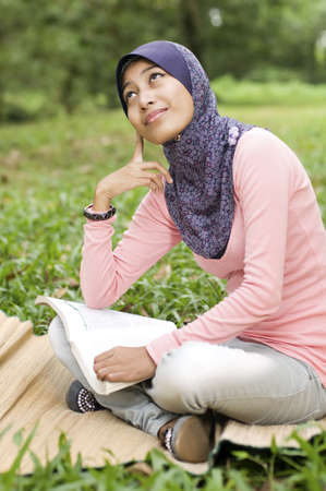 Beautiful young muslim lady thinking while holding book isolated green park