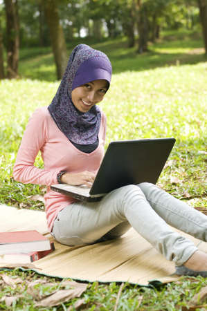 Beautiful young muslim lady typing on laptop while sit on the map in green garden photo