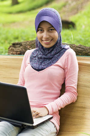 Beautiful young muslim smile infront of notebook. She lean again tree stump and sit on mat. photo