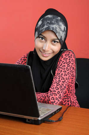 Beautiful young muslim smile  infront of notebook isolated red background photo