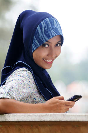 Beautiful young muslim smile while write text on mobile phone isolated blur park background photo