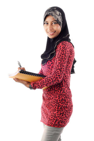 Beautiful young muslim smile while writing and hold books isolated white background Stock Photo