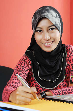 Beautiful young muslim smile while writing infront of notebook isolated red wall in office photo