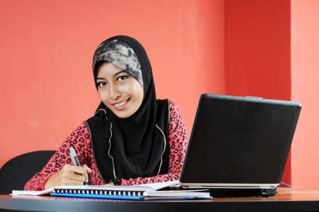 Beautiful young muslim smile while writing infront of notebook isolated red wall in office
