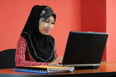 Beautiful young muslim woman with notebook with red background in an office environment photo