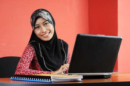 Mooie jonge moslim vrouw glimlachen terwijl het werken in kantoor met rode achtergrond