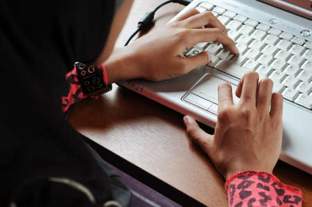 Muslim women hand typing on keyboard with red shirt and black jilbab