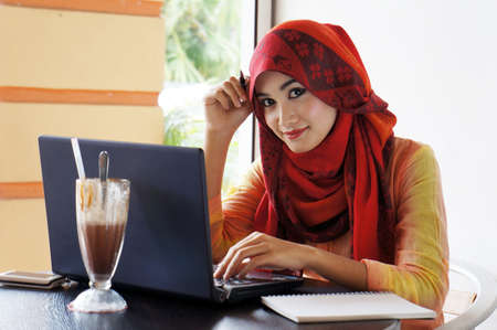 Stylish muslim woman wearing red scarf smiling while surfing at a cafe
