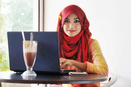 Stylish muslim woman wearing red scarf smiling while typing on her notebook at a cafe