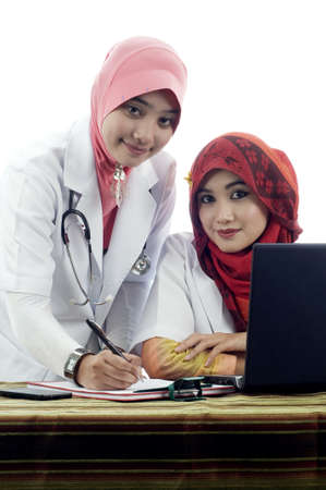 Two young muslim lady doctor in discussion isolated white background photo