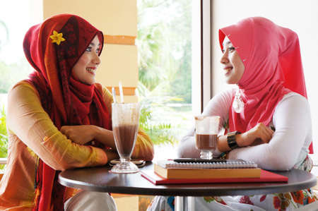 malay ethnicity: Two young stylish muslim women have a conversation at a cafe Stock Photo