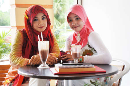 Two young stylish muslim women have a meet up at a cafe  Stockfoto